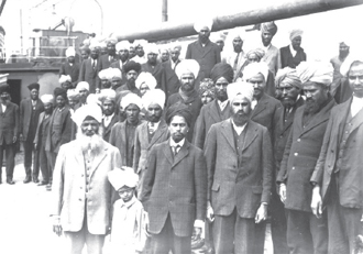 Gurdit Singh in the white suit with his son and fellow passengers, 1914