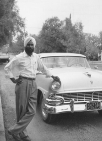 Jarnail Singh Purewal posing in front of his new car, Yuba City 1955