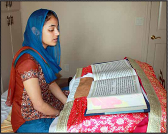 Sikh woman reading Siri Guru Granth Sahib in her home