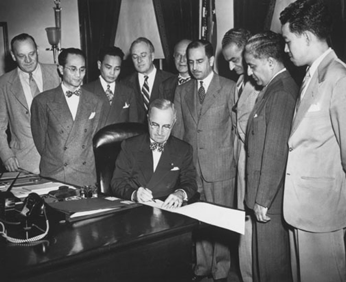President Harry Truman signs the Luce-Celler Bill